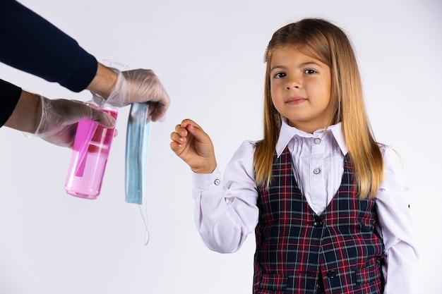 Menina caucasiana com uniforme escolar pega a máscara protetora e desinfeta as mãos, isoladas em