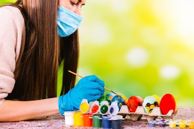 Menina caucasiana concentrada com máscara médica e luvas descartáveis decorando ovos artesanais para as férias pascal