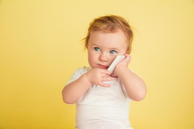 Menina caucasiana, crianças isoladas em amarelo