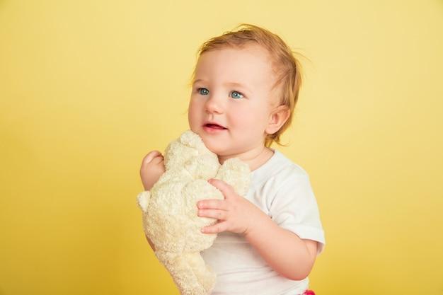 Menina caucasiana, crianças isoladas em fundo amarelo do estúdio. retrato de criança fofa e adorável, bebê brincando com o ursinho de pelúcia. conceito de infância, família, felicidade, nova vida, educação.