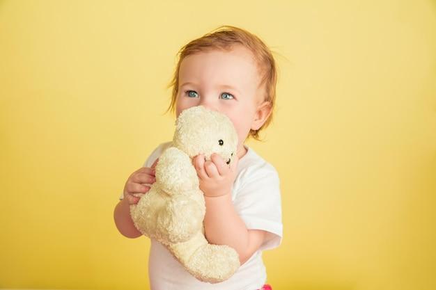 Menina caucasiana, crianças isoladas em fundo amarelo do estúdio. retrato de criança fofa e adorável, bebê brincando com ursinho de pelúcia.