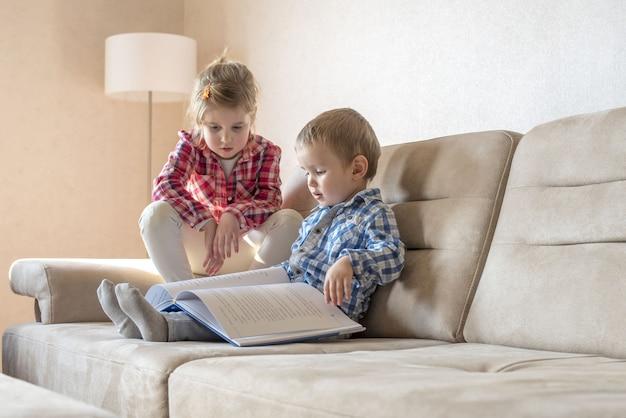 Menina caucasiana de 6 anos com o irmão de 4 anos lendo um livro no sofá de casa