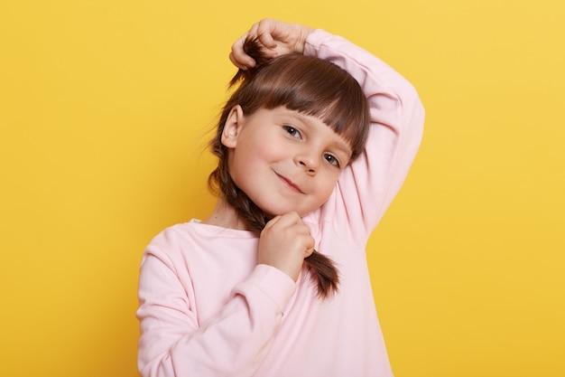 Menina caucasiana de cabelos escuros com tranças com expressão alegre, mantendo a mão na cabeça dela e tranças, sorriso encantador, criança pré-escolar usa camisa casual.