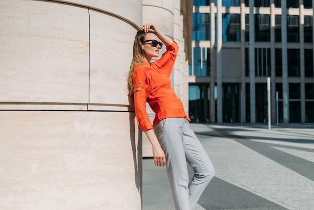 Menina caucasiana de comprimento total em óculos escuros e roupas casuais, apoiada em um prédio