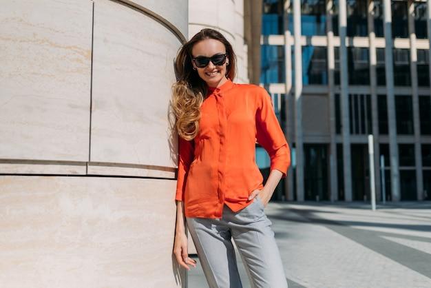 Menina caucasiana de óculos escuros e roupas casuais em uma cidade de verão