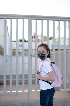 Menina caucasiana de olhos azuis esperando para entrar na escola no novo normal com uma máscara