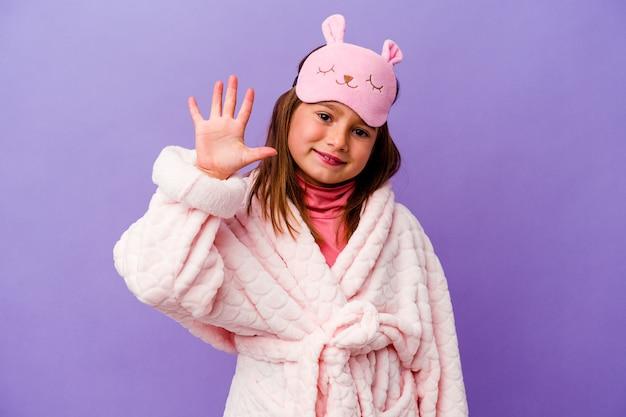 Menina caucasiana de pijama isolado na parede roxa, sorrindo alegre mostrando o número cinco com os dedos.