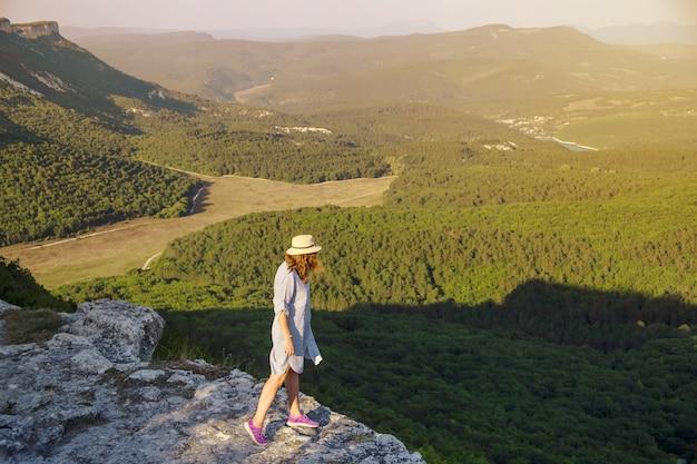 Menina caucasiana de vestido e chapéu fica no topo da montanha