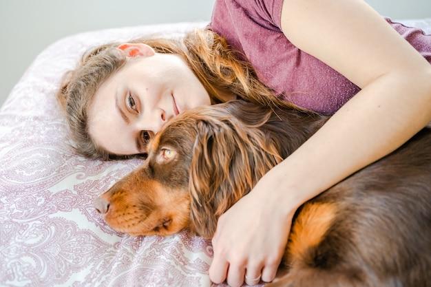 Menina caucasiana deitada na cama e abraçando o cachorro. palma de maiorca, espanha Foto Premium