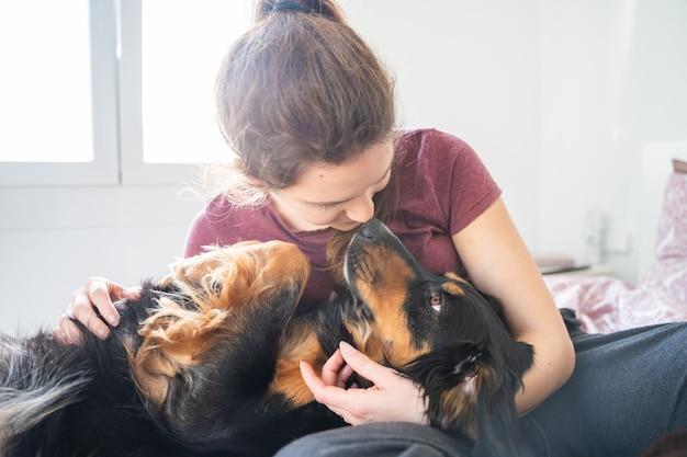 Menina caucasiana deitada na cama e abraçando o cachorro. palma de maiorca, espanha