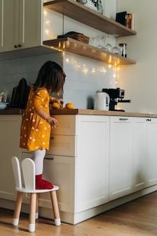 Menina caucasiana descascando tangerinas no balcão da cozinha. dieta de criança saudável. impulso imunológico com