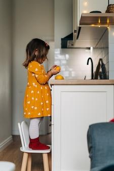 Menina caucasiana descascando tangerinas no balcão da cozinha. dieta de criança saudável. reforço imunológico com vitamina c. foto de alta qualidade