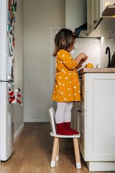 Menina caucasiana descascando tangerinas no balcão da cozinha.