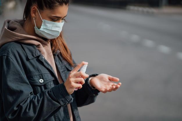 Menina caucasiana desinfeta as mãos com spray desinfetante.