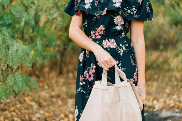 Menina caucasiana detém comprador de linho no pôr do sol ao ar livre