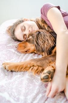 Menina caucasiana, dormindo na cama e abraçando o cachorro dela. palma de maiorca, espanha