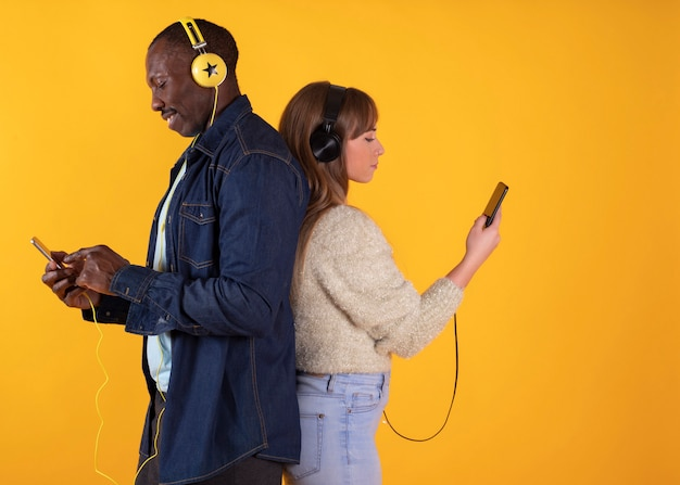 Menina caucasiana e homem africano, olhando para a tela de seus telefones inteligentes contra. rapaz americano com sua namorada ouvindo música e segurando telefones celulares