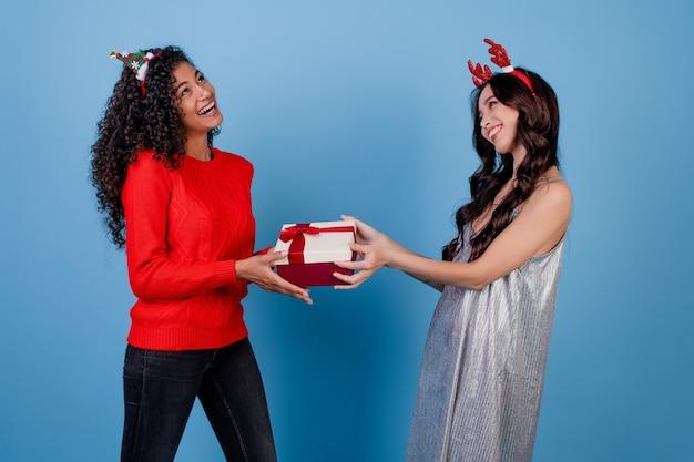Menina caucasiana e mulher negra com caixa de presente