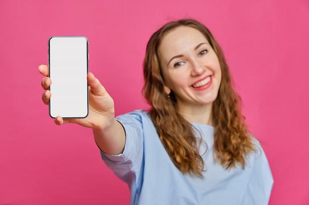 Menina caucasiana elegante em uma camiseta azul pálida detém um smartphone na mão e mostra para a câmera em um fundo rosa.