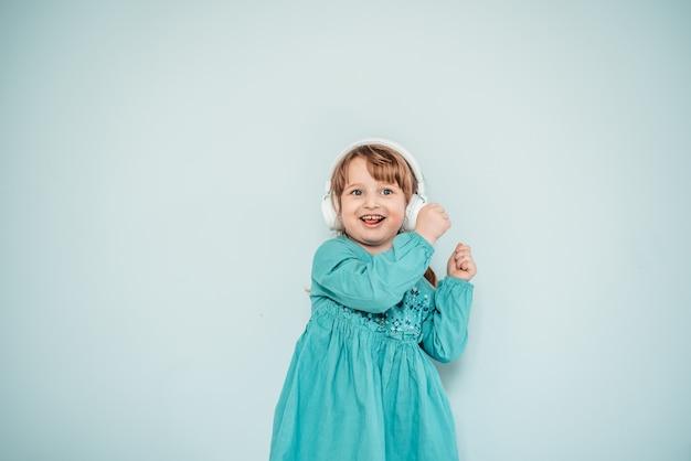 Menina caucasiana em fones de ouvido brancos ouve música e dança em um vestido azul turquesa brilhante.