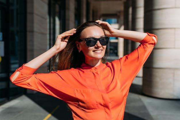 Menina caucasiana em óculos de sol e roupas casuais alegra-se com o tempo ensolarado.