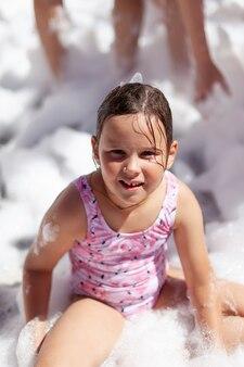 Menina caucasiana em um maiô rosa está sentada na espuma à beira da piscina em uma festa da espuma e dando uma chance ...