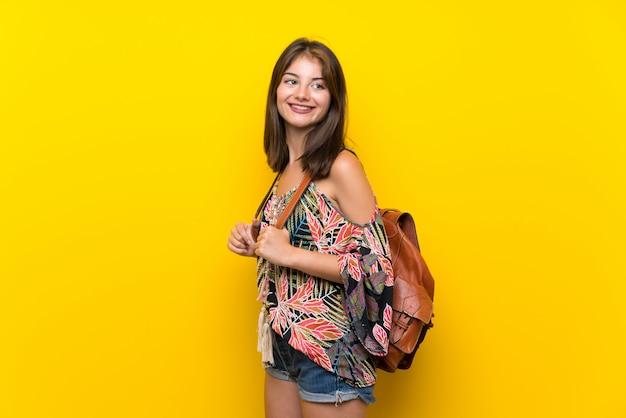 Menina caucasiana em vestido colorido com mochila