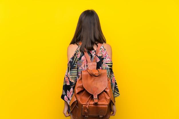 Menina caucasiana em vestido colorido isolado parede amarela com mochila