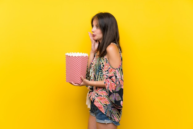 Menina caucasiana em vestido colorido isolado parede amarela segurando uma tigela de pipocas