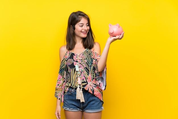 Menina caucasiana em vestido colorido, segurando um grande piggybank