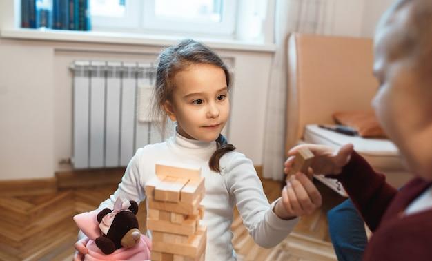 Menina caucasiana encantadora brincando de jenga com a mãe e o ursinho de pelúcia segurando um bloco de madeira