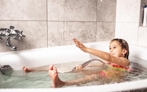 Menina caucasiana engraçada e emocional brincando com água com alegria