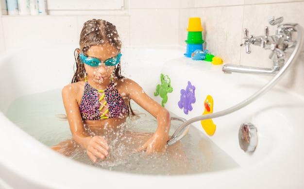 Menina caucasiana engraçada emocional brinca com água enquanto toma banho no banheiro. conceito de entretenimento e higiene de crianças saudáveis. copyspace