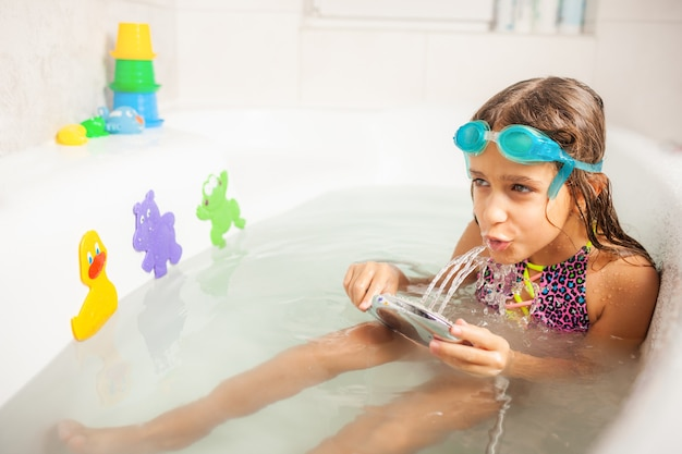 Menina caucasiana engraçada emocional brinca com água enquanto toma banho no banheiro. conceito de entretenimento e higiene de crianças saudáveis.