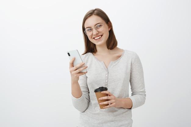 Menina caucasiana entusiasmada de aparência amigável de óculos com cabelo curto castanho segurando smarpthone e um copo de papel com café esperando um amigo no café e jogando no aplicativo usando um novo celular sobre a parede cinza