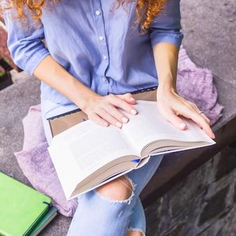 Menina caucasiana está lendo um livro educacional grosso enquanto está sentado ao ar livre