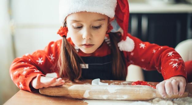Menina caucasiana está rolando a massa durante uma preparação de natal em casa vestindo roupas de papai noel
