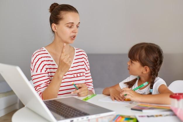 Menina caucasiana, estudando com a mãe ou professora na mesa de estudo com o laptop, livros e se divertindo aprendendo, mamãe explica as regras para a filha, educação online.