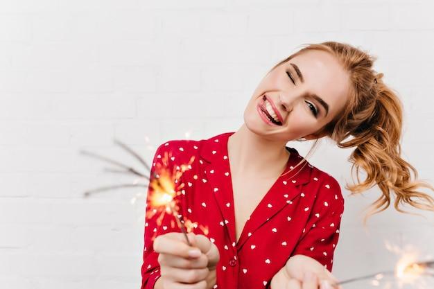 Menina caucasiana, expressando emoções positivas e acenando estrelinhas. maravilhosa moça rindo esperando o ano novo com luzes de bengala.