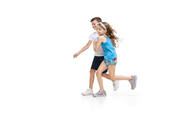 Menina caucasiana feliz e menino pulando e correndo, isolado no fundo branco