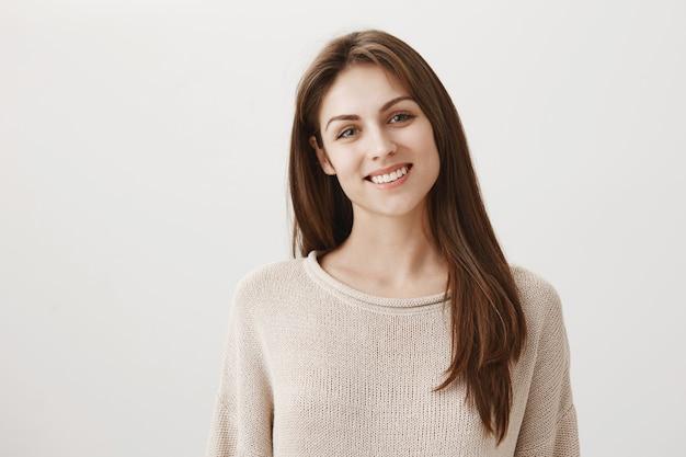 Menina caucasiana feliz sorridente e parecendo amigável