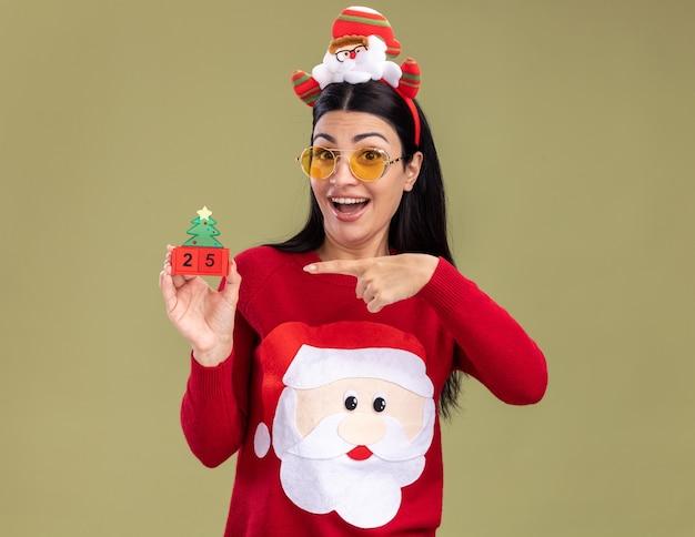 Menina caucasiana impressionada com bandana de papai noel e suéter com óculos segurando um brinquedo de árvore de natal com data apontando para ele, olhando para a câmera