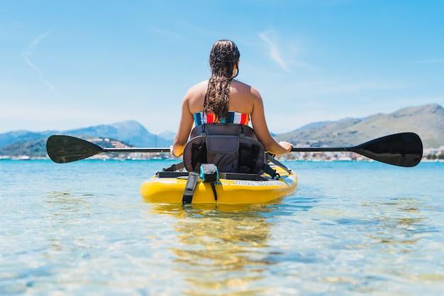 Menina caucasiana irreconhecível remando em uma prancha no mar - copyspace