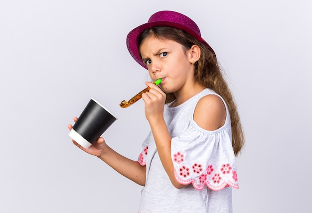 Menina caucasiana irritada com chapéu de festa roxo, soprando apito de festa e segurando um copo de papel isolado na parede branca com espaço de cópia