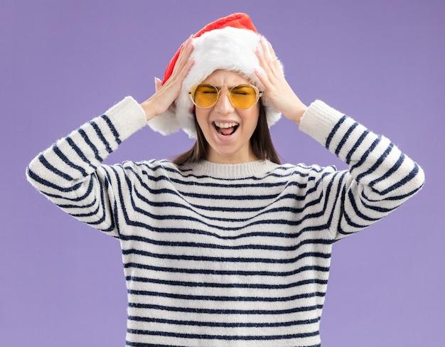 Menina caucasiana irritada com óculos de sol e chapéu de papai noel segurando a cabeça isolada na parede roxa com espaço de cópia