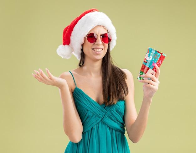 Menina caucasiana irritada com óculos de sol e chapéu de papai noel segurando um copo de papel
