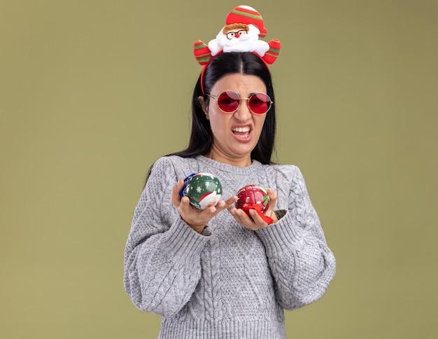 Menina caucasiana irritada com uma faixa de papai noel com óculos segurando enfeites de natal, olhando para a câmera isolada em fundo verde oliva