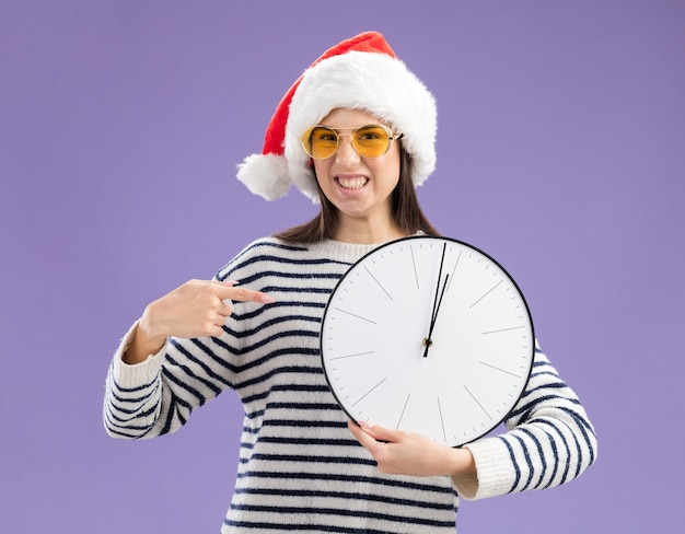 Menina caucasiana irritada de óculos de sol com chapéu de papai noel segurando e apontando para o relógio