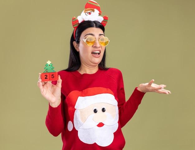 Menina caucasiana irritada usando bandana de papai noel e suéter com óculos segurando um brinquedo de árvore de natal com data olhando para o lado, mostrando a mão vazia isolada no fundo verde oliva