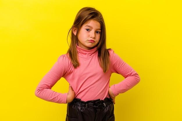 Menina caucasiana isolada em amarelo confusa, sente-se em dúvida e insegura.